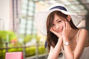 Fotos Asiatische Armbanduhr Unscharfer Hintergrund Der Hut Braunhaarige Blick Lächeln Hand junge frau
