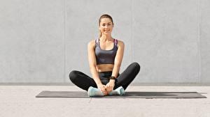 Bakgrundsbilder på skrivbordet Fitness Sitter Sportskor Ben Ett linne Leende Blick Unga_kvinnor
