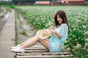 Fotos Asiatische Sitzt Kleid Bein Der Hut Blick Braunhaarige junge frau