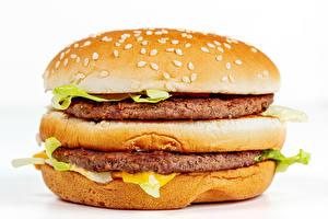 Bureaubladachtergronden Fastfood Hamburger Zoete broodjes Frikadellen Close-up Witte achtergrond Voedsel