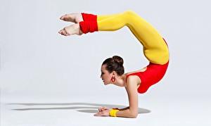 Hintergrundbilder Gymnastik Grauer Hintergrund Braune Haare Posiert Bein Mädchens