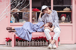 Photo Asiatic Bench Sitting Esting 2 Gown Jeans Formal shirt Baseball cap Glance young woman