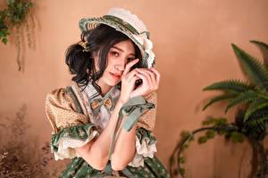 Desktop wallpapers Asian Brunette girl Gown Hat Hands Staring young woman