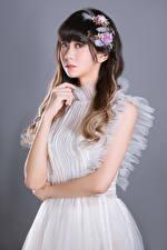 Fotos Asiaten Süßes Pose Kleid Hand Starren Grauer Hintergrund Mädchens