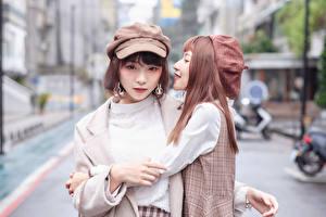 Tapety na pulpit Azjaci Przytulania Dwa 2 Rozmazane tło Spojrzenie Czapka z daszkiem Dziewczyny