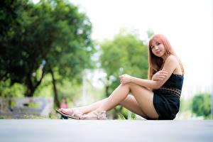 Tapety na pulpit Azjaci Uśmiech Rozmazane tło Ręce Nogi Siedzi młoda kobieta