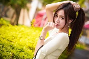 Fotos Asiatisches Armbanduhr Braune Haare Hand Starren Unscharfer Hintergrund Mädchens