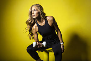 Wallpaper Fitness Colored background Sitting Brown haired Staring Singlet Hands Dumbbell young woman