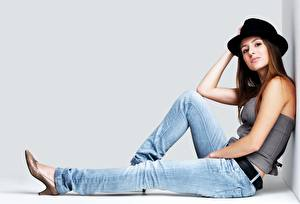 Wallpapers Gray background Brown haired Hat Sitting Hands Legs Jeans Girls