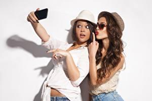 Tapety na pulpit Dwie Selfie Poza Brązowowłosa dziewczyna Kapelusz Okulary Ręce Białe tło młode kobiety
