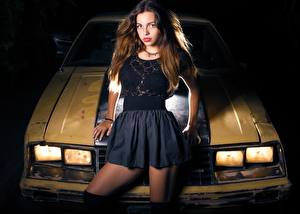 Picture Brown haired Glance Hands Headlights Skirt young woman Cars