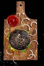 Fotos Fast food Hamburger Schwarzer Hintergrund Schneidebrett Ketchup Getreide Schwarz