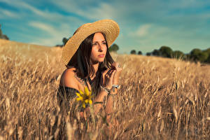 Pictures Fields Brunette girl Hat Spikes Hands Glance female