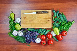 Desktop wallpapers Knife Vegetables Cucumbers Tomatoes Bell pepper Garlic Dill Wood planks Cutting board Food