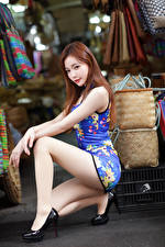 Pictures Asiatic Brown haired Gown Sitting Legs High heels Staring young woman