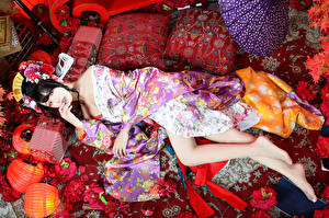 Picture Asiatic Brunette girl Lying down Kimono Pillows Legs Glance young woman