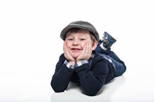 Bilder Jungen Liegen Baseballkappe Lächeln Blick Weißer hintergrund kind