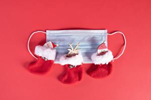 Bureaubladachtergronden Kerst Coronavirus Maskers Een hert Rode achtergrond Kerstman Sneeuwpop Een laars