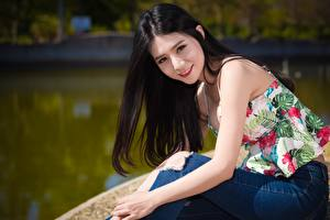 Wallpapers Asian Brunette girl Glance Smile Hands Sitting Jeans Bokeh young woman