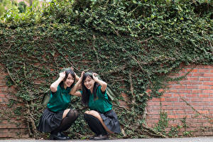 Fotos Asiaten Brünette Zwei Lächeln Sitzend Uniform Schulmädchen Mädchens