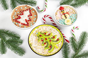 Pictures Christmas Lollipop Creative Oatmeal Muesli Kiwi Pomegranate White background Branches Christmas tree Snowman