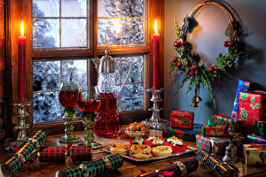 Pictures New year Still-life Candles Wine Little cakes Branches Balls Present Pitcher Stemware Window Food