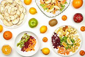 Image Fruit Mandarine Apples Lemons Chinese gooseberry Pomegranate White background Plate Sliced food Food