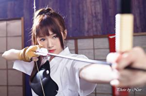 Images Asiatic Archers Staring Hands Brown haired Bow weapon Wooden arrow young woman
