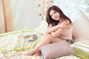 Desktop wallpapers Asian Bed Pillows Brown haired Hands Sitting young woman