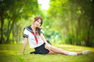 Desktop hintergrundbilder Asiaten Unscharfer Hintergrund Sitzt Gras Lächeln Uniform Krawatte Schülerin Mädchens