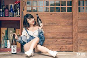 Bilder Asiaten Flasche Brünette Sitzend Lächeln Bein junge Frauen