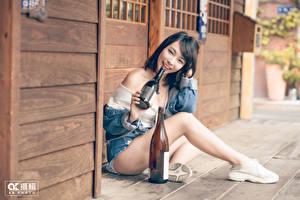 Hintergrundbilder Asiatische Brünette Lächeln Flasche Sitzend Bein