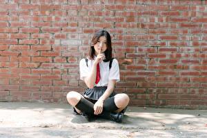 Images Asiatic Gestures Walls Made of bricks Sit Brunette girl Necktie Hands Legs Knee highs young woman