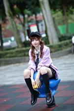 Fotos Asiaten Sitzt Baseballkappe Bein Blick Bokeh Mädchens