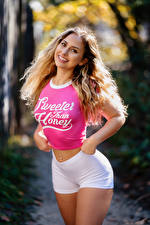 Images Blurred background Pose Smile T-shirt Text English Shorts Staring young woman