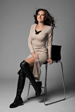 Picture Brown haired Chairs Sit Gown Wearing boots Legs Glance young woman
