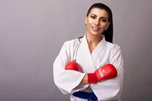 Hintergrundbilder Grauer Hintergrund Brünette Starren Lächeln Kimono Hand Handschuh Karate Mädchens