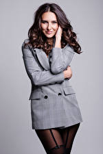Pictures Modelling Brown haired Smile Suit jacket Glance Pantyhose Gray background young woman