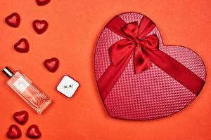 Bilder Valentinstag Bonbon Farbigen hintergrund Geschenke Herz Schleife Parfüm Roter Hintergrund Lebensmittel
