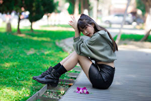 Image Asian Blurred background Sit Legs Boots Skirt Staring young woman