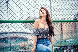 Sfondi desktop Asiatico Ragazza capelli castani Colpo d'occhio Sedute Braccia Scollatura Jeans giovani donne