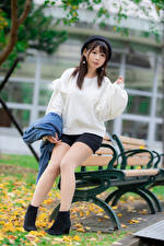 Pictures Asiatic Brunette girl Bench Sitting Sweater Beret Staring Bokeh young woman