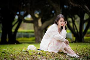 Pictures Asiatic Brunette girl Bokeh Hat Sit Hands Legs young woman