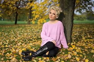 Images Autumn Grass Foliage Blonde girl Sweater Sitting Hands Legs Wearing boots Girls