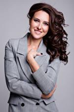 Hintergrundbilder Braune Haare Lächeln Sakko Hand Blick Grauer Hintergrund junge Frauen
