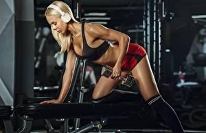 Bilder Fitness Blond Mädchen Fitnessstudio Hantel Trainieren Kopfhörer junge Frauen Sport