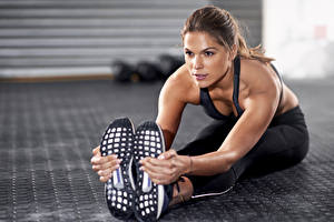 Photo Fitness Brown haired Sit Stretching Workout Staring Hands Legs Athletic shoe Shoe sole young woman