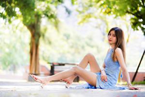 Fotos Asiatisches Unscharfer Hintergrund Sitzt Kleid Bein Starren Mädchens