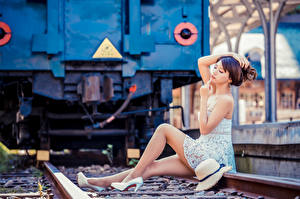 Pictures Asian Blurred background Sit Frock Legs Rails Hat Posing Girls