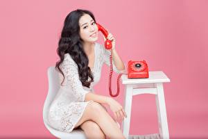 Bakgrundsbilder på skrivbordet Asiater Rosa bakgrund Brunett tjej Telefon Sitter Leende Händer Klänning ung kvinna